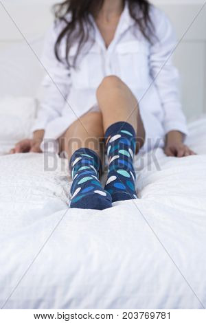woman with a white shirt and coloured socks sitting on bed.