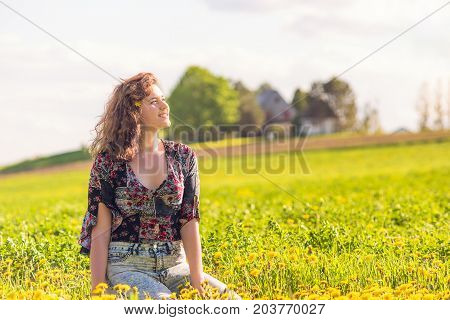 Portrait Of Young Smiling Woman Sitting In Yellow Dandelion Farm Field During Sunset By House In Ile