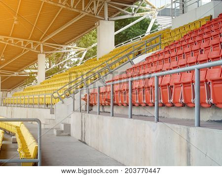empty orange and yellow grandstand seats in sports arena with evening sunlight, in a day without sports competition