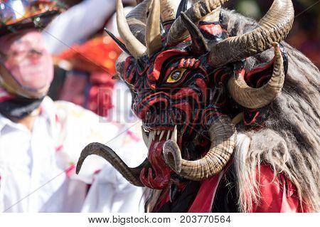 June 17 2017 Pujili Ecuador: closeup of a male dancer with colorful traditiona face mask worn at the Corpus Christi annual parade