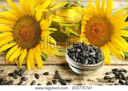 Sunflower Seeds In Bowl With Glass Of Oil On Wooden Table