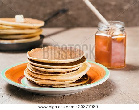Close up view of homemade pancakes. Stack of pancakes with honey on brown concrete background.