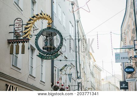 Austria, Salzburg, January 1, 2017: Advertising signs of shops on Getreidegasse street. A picturesque street on the territory of the old city, long considered to be the center of trade of Salzburg.