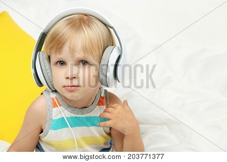 Little Boy Sitting With Headphones In White Bed