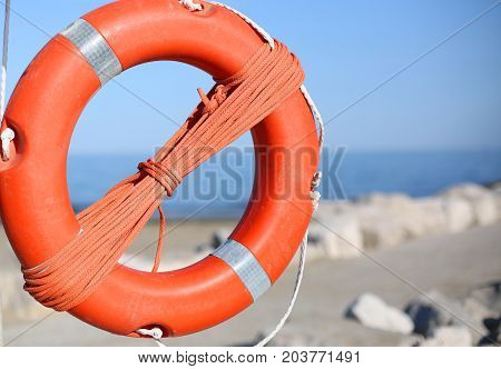 Orange Lifebuoy For People Near Rocks At The Sea
