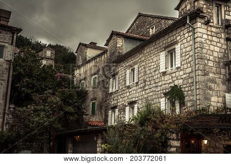 Vintage medieval city street with stone building exterior in overcast day during raining autumn season in old European city Perast with medieval architecture