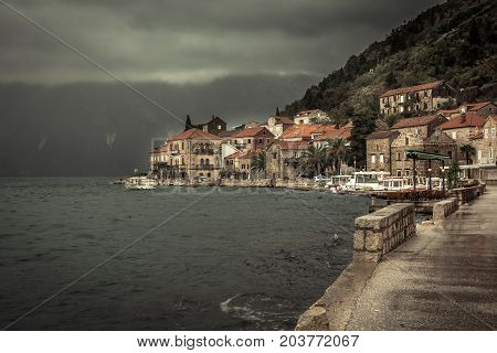 Promenade in old medieval town Perast in rainy overcast day with puddles in Montenegro