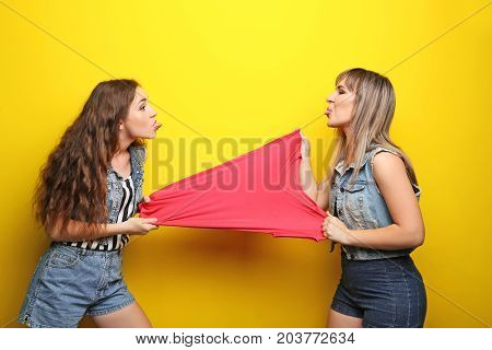 Two Young Woman Having Quarreling On Yellow Background