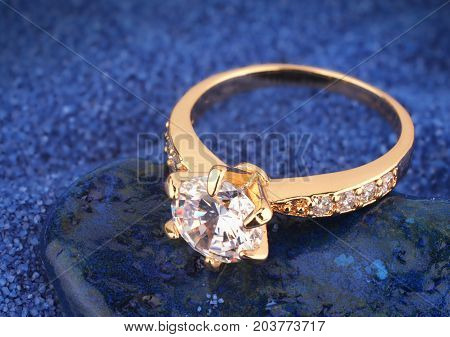 golden Jewelery ring with diamond on blue background