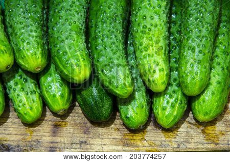 Wet cucumbers are tiered on a board.