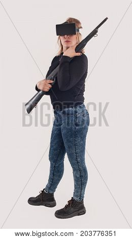 Woman play VR shooter game with vr glasses and rifle. Studio shoot