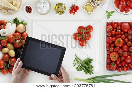 hands with digital tablet above on white cutting board with vegetables and tomatoes food ingredients on kitchen white worktop copy space top view