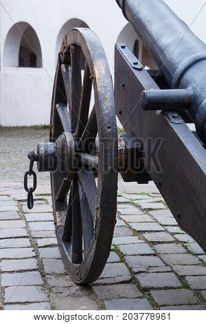 Wheel of ancient cannon with chain close up. Black colored cannon.