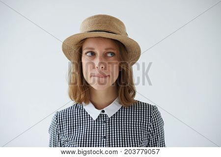 Studio shot of beautiful hesitated young female wearing stylish round hat and dress looking uncertain and confused biting lips while thinking something over having doubts about making decision