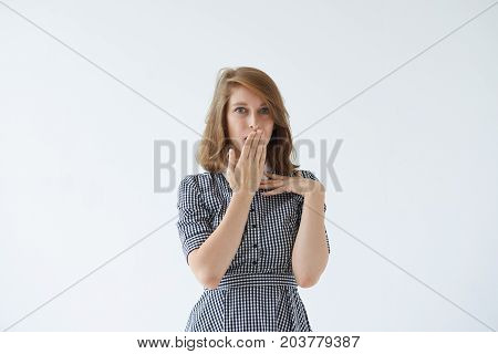 Body language. Surprised amazed young female in dress covering mouth with hand and saying Oops staring at camera in shock and full disbelief. Cute blue-eyed woman repenting after she made mistake