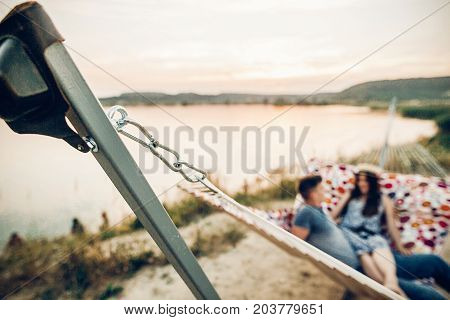 Travel Hammock. Happy Hipster Couple Relaxing In Hammock In Sunset Light On The Beach, Summer Vacati