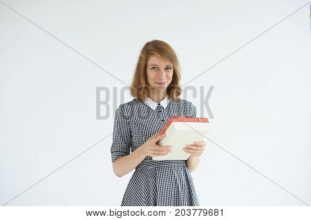 Isolated studio shot of happy young European woman wearing romantic dress smiling cheerfully holding box of delicious chocolate candies flattered with unexpected pleasant gift from her boyfriend
