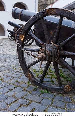 Ancient cannon on wheels close up and two cannons background. Bottom view