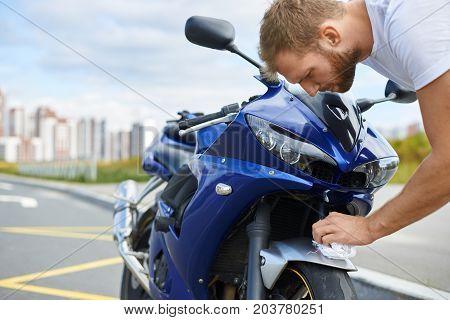 Cropped outdoor portrait of handsome bearded young European man cleaning blue motorcycle using white microfiber cloth standing on empty parking lot with urban setting in background. Valeting concept
