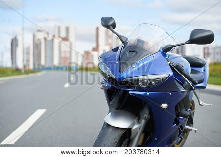 Outdoor pciture of custom-built motorcycle parked on road against blue sky and modern high-rise buildings background. Motorcycling transport transportation lifestyle extreme and hobby concept
