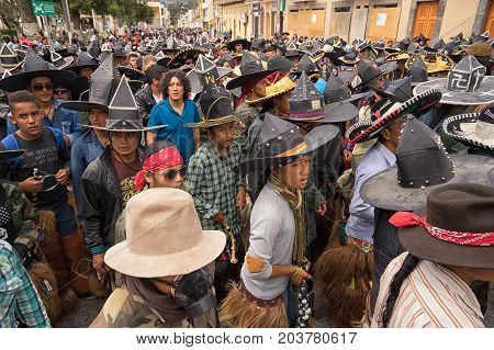 June 25 2017 Cotacachi Ecuador: male indigenous dancers in a compact formation during the 'occupy the plaza' parade during Inti Raymi