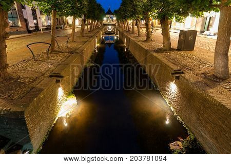The typical old Dutch city canals with reflections in the water. A long exposure shot at the blue hour after sunset.
