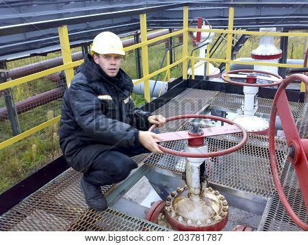 The Man In The Overalls Of Rosneft. The Operator Turns The Handwheel Of The Valve On The Pipeline.