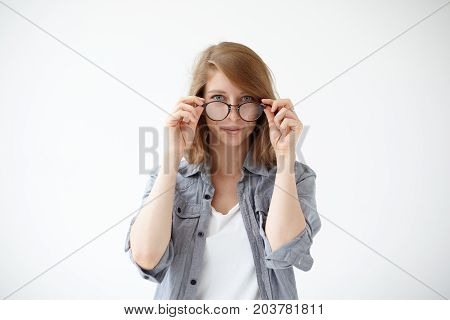 Waist up portrait of smiling casually dressed young female with bob hairstyle peering at camera from behind her trendy eyewear. Cute girl posing at white studio wall wearing stylish eyeglasses