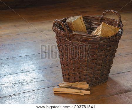 wicker basket with chopped wood and splinter pile on wooden board floor