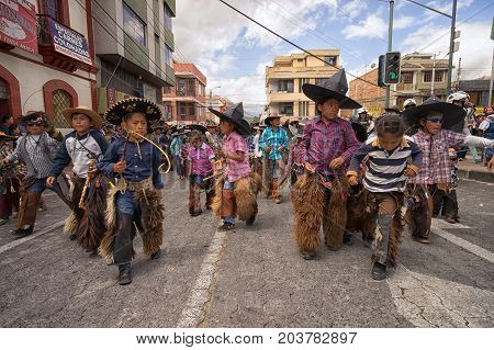 June 25 2017 Cotacachi Ecuador: indigenous quechua children wearing sombreros and chaps dancing at the Inti Raymi celebrations