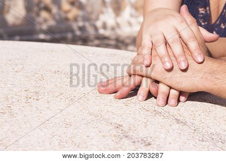 Hands of man and woman intertwined in affectionate attitude
