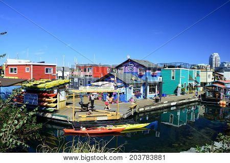 Victoria BC,Canada,August 10 2015.The picturesque Fisherman's Wharf with interesting shops and restaurants is a busy stop for tourists when in Victoria.Come visit Victoria and Fisherman's Wharf,rent a kayak and explore the inner harbor.