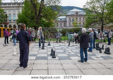 SARAJEVO BOSNIA AND HERZEGOVINA - APRIL 15 2017: Old men playing a giant chess game in the city center of Sarajevo capital city of Bosnia. This chess game is one of the symbols of the life in the city