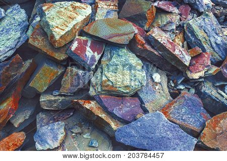 Layers of toning colored stones. A big heap of sandstones, storage space of various fantastic sandstone. Cracks and layers of sandstone background. The pattern of the variegated sandstone