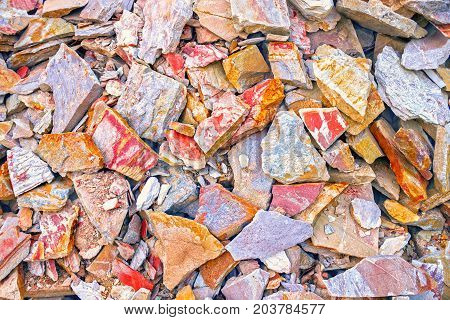 The pattern of the variegated sandstone. A big heap of sandstones, storage space of various natural sandstone. Cracks and colorful layers of sandstone background. Layers of toning colored stones