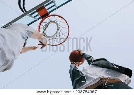 Cut view of a small competition between two friends that like to play basketball. They are in the action of throwing the ball into the basket. Close up
