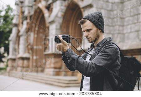Talented and professional photographer is travelling this city and taking some pictures of people and landscapes of this city. He is very concentrated on what he is doing. Close up. Cut view