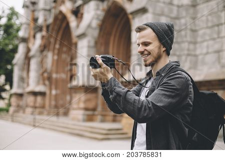 The photo of a tourist that likes to take pictures of city landscapes. He is standing near the old building and taking the pictures with passion and pleasure. Close up. Cut view