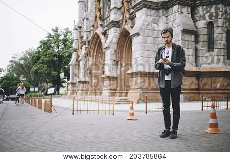 Experienced traveller has made a stop on the sidewalk near the old church. He is not sure where he is right now so that's why the guy decided to check his current position on the phone.