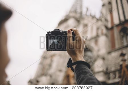 The picture of a young tourist that likes to take some pictures during the trip. We can see how he is shooting the church that is located nearby. He is professional because he can shoot with one hand. Close up. Cut view
