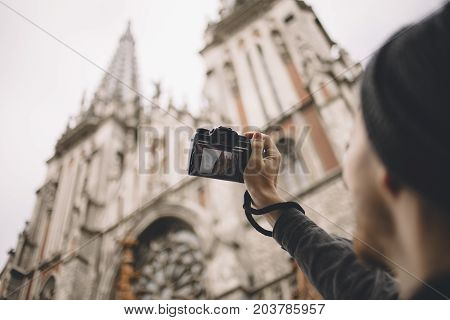 Experienced traveller is taking some pictures of old church that is located in this city. The guy liket to shoot this great building. Close up. Cut view