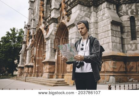 A picture of tourist standing near the big old building and looking to the map. Seems like this guy has lost in the big city and now he is trying to find his current location.