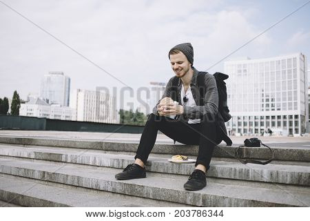 The traveller is sitting on the steps after the long trip and holding the burger in his hands. He is so hungry that he can't wait to devour the lunch. The guy is tired but he looks happy