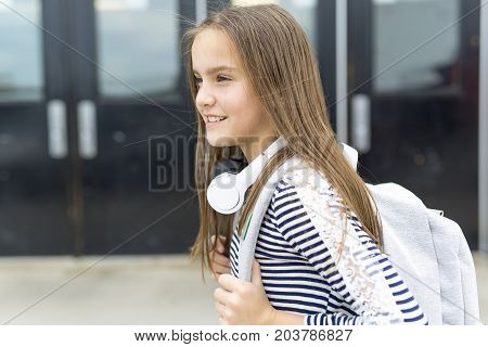 An Elementary school pupil outside carrying rucksack