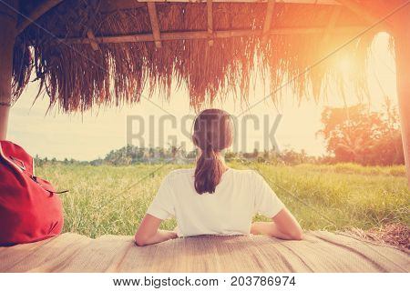 Young girl resting and listening music with headphones in nature intentional sun glare and vintage color