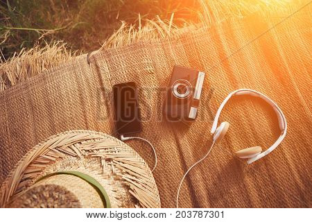 Mobile phone, vintage photo camera, headphones and hat in nature intentional sun glare