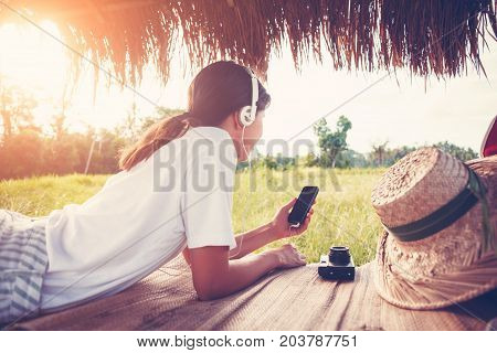 Young girl resting outdoors with mobile phone in hands and listening music with headphones intentional sun glare