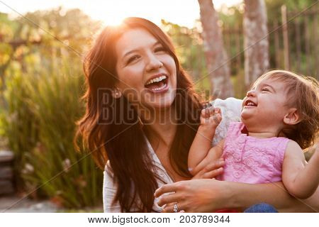 Hispanic mother and daughter smiling and playing outside.
