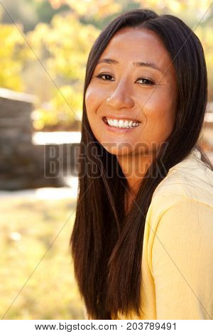Beautiful happy Asian woman smiling sitting outside.