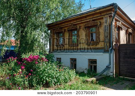SUZDAL/ RUSSIA - AUGUST 19, 2017. Old Russian wooden residential building with flowers in front of it. Suzdal, Vladimir region, Russia.
